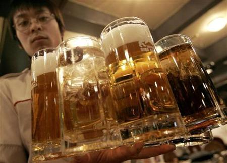 A waiter holds mugs filled with beer at Sapporo Bier Garten in Sapporo, Japan, February 19, 2007. REUTERS/Yuriko Nakao