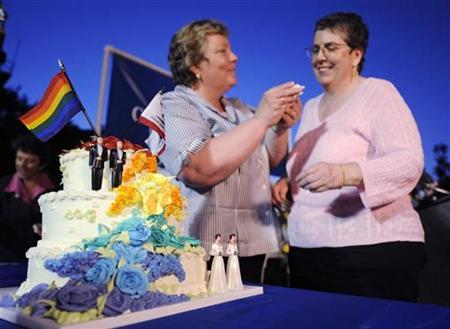 Lorri L. Jean (L) and Gina Calvelli (R) share a piece of wedding cake at a demonstration celebrating the California Supreme Court's decision overturning a ban on same-sex marriages held in West Hollywood, California on May 15, 2008. REUTERS/Phil McCarten