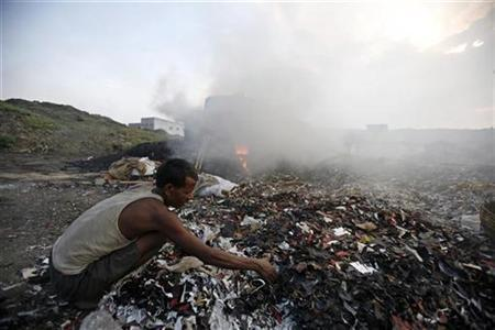 A labourer works beside a burning oven to make fertilizer ingredients out of scrap leather at a roadside factory in Kolkata May 4, 2007. REUTERS/Parth Sanyal