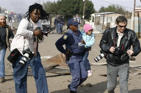 Reuters photographer Siphiwe Sibeko (L) is seen in action during the recent xenophobic attacks in Reiger Park, east of Johannesburg, May 19, 2008. Picture taken May 19, 2008. REUTERS/Stringer