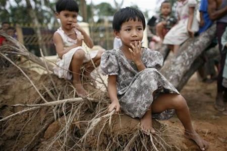 Children wait while rice is handed out near Kundangon May 11, 2008. REUTERS/Stringer