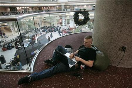 Private Gregory Jones traveling home from Fort Benning, finds a quiet place to send emails above the atrium at Hartsfield-Jackson Atlanta International Airport in Atlanta, Georgia, November 21, 2007. REUTERS/Tami Chappell