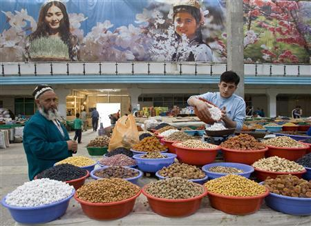 A vendor (R) sells dried fruit at a market in Dushanbe, Tajikistan, May 27, 2008.