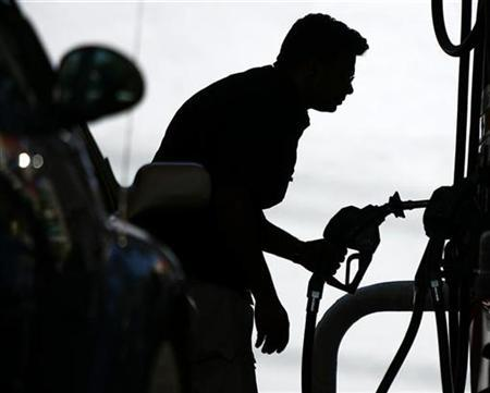 A resident looks at the price of gasoline at a gas station in Miami's South Beach, Florida April 23, 2008. REUTERS/Carlos Barria
