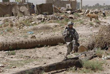 A U.S. soldier from Bravo Company, 1-22 Infantry Battalion provides security as his comrades conduct house-to-house search on the edge of Shiite dominated Baghdad's neighbourhood of Shulla, May 21, 2008. REUTERS/Oleg Popov