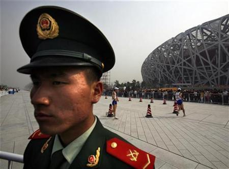 A paramilitary policeman stands guard as competitors in the Good Luck Beijing Race Walking Challenge pass the National Stadium, also known as the Bird's Nest, in Beijing April 18, 2008. REUTERS/David Gray