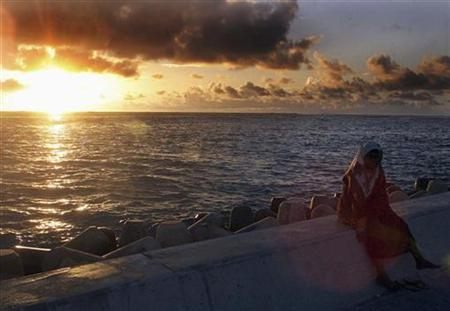 A woman sits atop a section of a dyke built to protect the tiny island from the ravages of the sea during a sunrise in the Maldives capital Male in this July 12, 2001 file photo. REUTERS/Anuruddha Lokuhapuarachchi