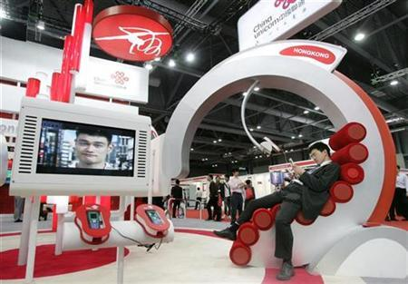 A visitor sits at a China Unicom's booth during the third day of the International Telecommunication Union (ITU) Telecom World 2006 in Hong Kong December 6, 2006. REUTERS/Paul Yeung