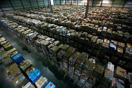A worker carries boxes through the Amazon warehouse in Milton Keynes, England, November 30, 2007. REUTERS/Kieran Doherty
