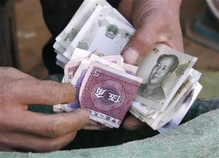 A vendor counts yuan notes at a market in Beijing November 23, 2007. REUTERS/Claro Cortes IV