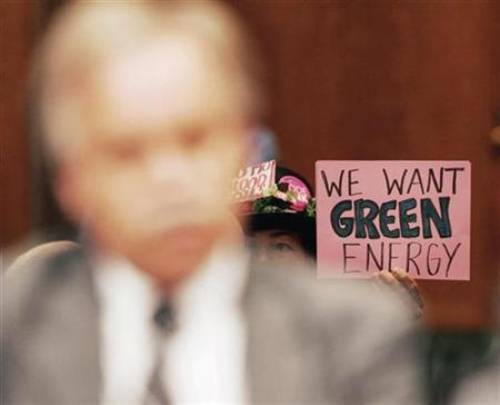 A protester holds a sign during testimony about the rising cost of gas prices before the Senate Judiciary Committee on Capitol Hill, May 21, 2008. REUTERS/Larry Downing