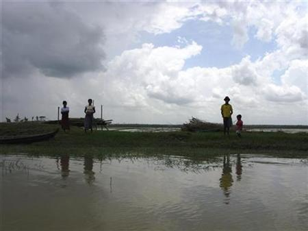 A family looks for traces of their house, on a marooned embankment, in the village of Pay Kunhnasay in the Kawhmu township, Myanmar, May 30, 2008. REUTERS/Aung Hla Tung