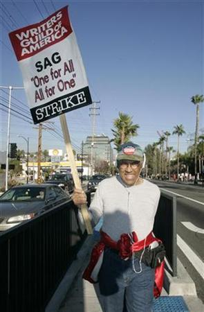 Screen Actors Guild member Enos Doyle carries a sign on the picket line at NBC studios in support of striking members of the Writers Guild of America in Burbank, California February 8, 2008. REUTERS/Fred Prouser