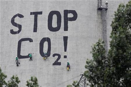 Greenpeace activists paint a slogan reading ''Stop CO2'' on one of the smoke stacks at the Belchatow power plant in Rogowiec near Belchatow, about 177 km (110 miles) from Warsaw July 3, 2007. REUTERS/Kacper Pempel