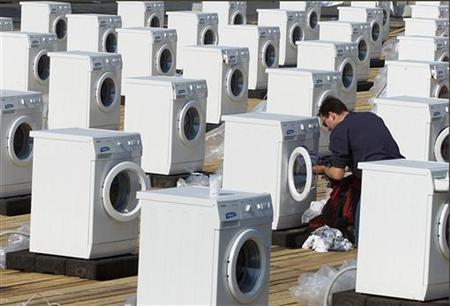 A man puts his laundry into a washing machine, part of an art istallation in Berlin's city center, in a file photo. REUTERS/File