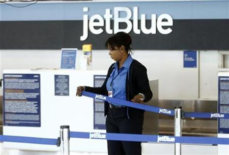 In this file photo an employee of JetBlue closes her station at JFK International Airport in New York February 19, 2007. JetBlue Airways Corp's LiveTV unit said it has agreed to buy Verizon Communications Inc's Airfone network as aims to develop in-flight email and Internet services, The Wall Street Journal said on Monday. REUTERS/Keith Bedford