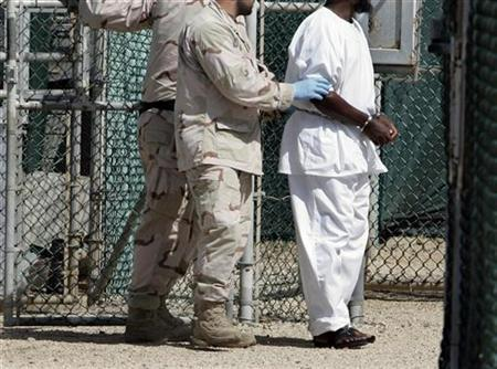 A detainee is escorted by U.S. Navy guards in Camp Four, the facility containing the ''most compliant'' detainees, at the Guantanamo Bay Naval Station in Guantanamo Bay, September 4, 2007. REUTERS/Joe Skipper