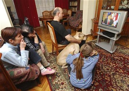 A Georgian family watches President Saakashvili's interview on television in their apartment in Tbilisi November 4, 2007. REUTERS/Irakli Gedenidze
