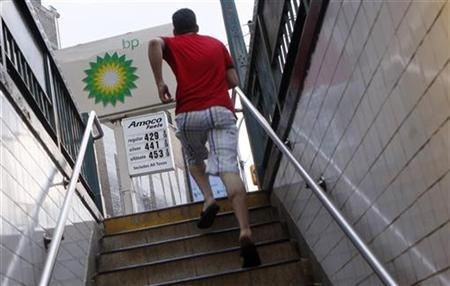 A commuter exits a subway station as fuel prices at a BP petrol station are advertised in New York June 8, 2008. . REUTERS/Joshua Lott