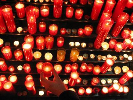A man offers candles in a file photo. REUTERS/Gustau Nacarino