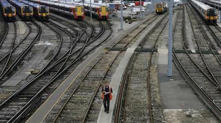 A worker walks alongside tracks near Clapham Junction station in London June 6, 2008. REUTERS/Luke MacGregor