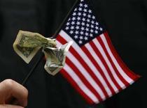 <p>Banconota da un dollaro legata a una bandiera degli Stati Uniti, durante una cerimonia di laurea alla Business School di Harvard. REUTERS/Brian Snyder (Usa)</p>