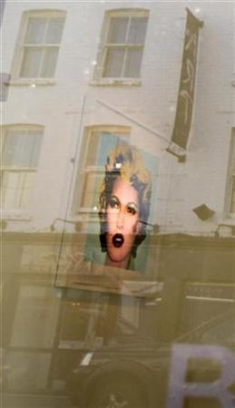 A portrait of model Kate Moss titled ''Kate (Original Colourway)'' by British artist Banksy is photographed through the Andipa Gallery front window that reflects the buildings opposite in central London January 27, 2008. Nestled on Walton Street in London's stylish Knightsbridge, the Andipa Gallery is taking delivery of life-sized prints, newsprint sculptures and mammoth murals from New York, Los Angeles and Paris. REUTERS/Kieran Doherty