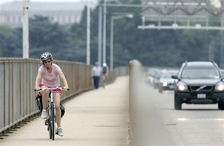 A cyclist crosses the 14th Street Bridge connecting Washington DC (rear) to Virginia as she leaves U.S. capital June 11, 2008. REUTERS/Hyungwon Kang