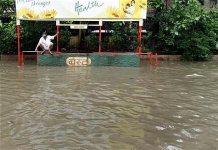A man sits at a flooded bus-stop after heavy rains in Mumbai in this file photo from August 3, 2007. Mumbai city officials are upset by an American warning about the risks of falling into manholes in India's commercial capital during the monsoon season. REUTERS/Punit Paranjpe