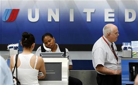 United Airlines employees work behind a check-in counter at the O'Hare International airport in Chicago June 4, 2008. REUTERS/Jeff Haynes