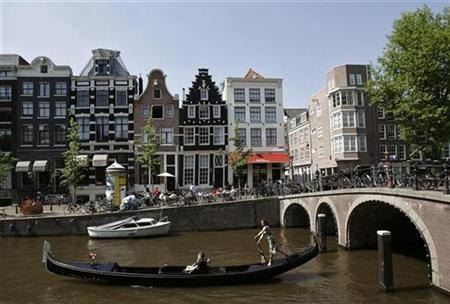 A woman rows her gondola through the canals of central Amsterdam May 9, 2008. A commercial network launched in Amsterdam on Tuesday is the first in Europe to use a mobile version of the Wimax standard to allow users to surf the Web at high speeds while on the move, operator Worldmax said. REUTERS/Robin van Lonkhuijsen/United Photos