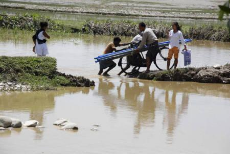 Flood-affected people cross a flooded paddy field in Lakhimpur district, about 400 km east of Guwahati, June 16, 2008. REUTERS/Stringer