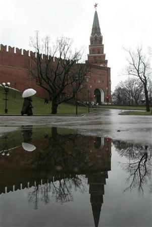 A woman with an umbrella walks past the Kremlin wall on a rainy day in Moscow January 19, 2007. REUTERS/Mikhail Voskresensky