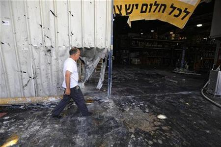 An Israeli man walks at the scene of a mortar attack in a paint factory in kibbutz Nir Oz, just outside the southern Gaza Strip June 5, 2008. REUTERS/Amir Cohen