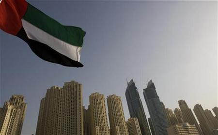 The United Arab Emirates flag flies in front of the Jumeirah Beach Residence in Dubai December 2, 2007. REUTERS/Steve Crisp