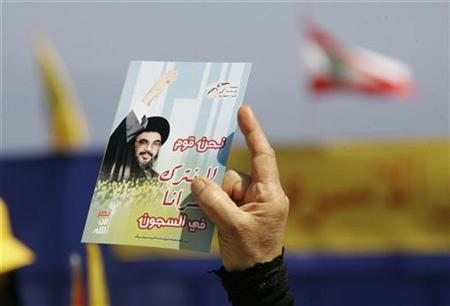 A Lebanese Hezbollah supporter holds a poster of Hezbollah leader Sayyed Hassan Nasrallah during a celebration in Naqoura village in south Lebanon to mark the release of Nissim Nasser after a six-year jail term in Israel June 1, 2008. REUTERS/Ali Hashisho