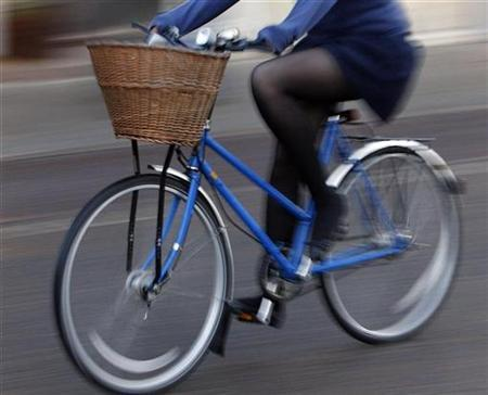 A woman rides a bicycle in Cambridge, central England in this February 20, 2008 file photo. REUTERS/Darren Staples/Files