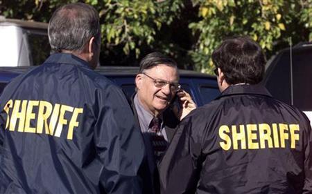 Maricopa County Sheriff, Joe Arpaio, (C) talks with investigators in Mesa, Arizona in this December 10, 2002 file photo. REUTES/Jeff Topping