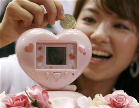 Bandai Co's employee Reiko Hirai demonstrates the company's latest electronic piggybank ''ikemenbank'' at the International Tokyo Toy Show in Tokyo June 19, 2008. ''Ikemenbank'', or ''handsome men bank'', is a heart-shaped electronic piggy bank with an LCD screen that allows its owner to conduct a virtual affair with a cartoon character while watching the coins pile up. REUTERS/Toru Hanai