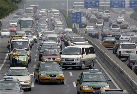 A traffic policeman on duty directs a vehicle to the side on 2nd Ring Road during rush hour in Beijing June 20, 2008. REUTERS/Jason Lee