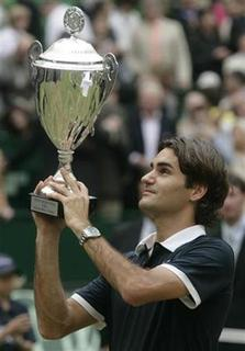 Roger Federer of Switzerland lifts the winner's trophy after beating Philipp Kohlschreiber of Germany in the final of the Halle Open ATP tennis tournament in Halle June 15, 2008. Federer will begin his quest for a sixth consecutive singles title at Wimbledon with a first round match against experienced Slovak Dominik Hrbaty. REUTERS/Wolfgang Rattay