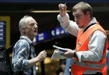 <p>Работник железнодорожной службы города Берна (справа) разговаривает с пассажиром после отключения электричества 23 июля 2007 года. Работникам швейцарских железнодорожных служб придется снять форменные оранжевые жилеты после того, как некоторые голландские поклонники футбола приняли их за себе подобных. (REUTERS/Stefan Wermuth)</p>