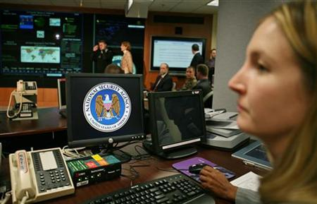 An employee at the National Security Agency (NSA) sits at her computer terminal in the Threat Operations Center in a file photo. The House of Representatives passed a bill on Friday that could shield phone companies from billions of dollars in lawsuits for their participation in the warrantless surveillance program begun by President Bush after the September 11 attacks. REUTERS/Jason Reed