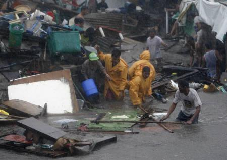 People living in a coastal area try to move their belongings to higher ground as Typhoon Fengshen rolls over in Navotos, Manila June 22, 2008. REUTERS/Darren Whiteside