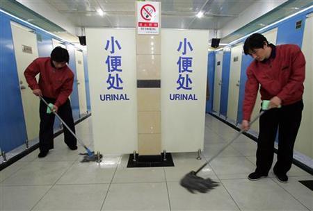 Cleaners mop the floor inside a public bathroom in Beijing, November 18, 2004. REUTERS/Claro Cortes IV