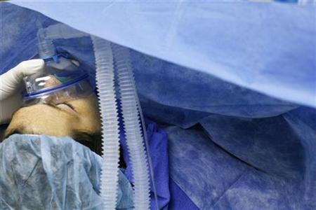 Anesthesiologist Ronald Milan checks the oxygen supply going to a patient during an abdominoplasty (tummy tuck) procedure at the Plastic Surgery Center in Shrewsbury, New Jersey October 22, 2007. REUTERS/Lucas Jackson