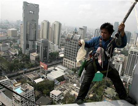 A window cleaner prepares to scale down a skyscraper in Bangkok February 11, 2008. REUTERS/Sukree Sukplang