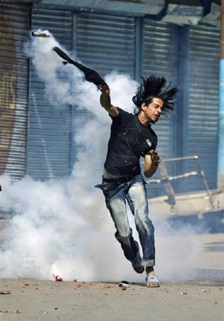 A Kashmiri Muslim protester throws back a tear gas shell towards Indian police during a protest in Srinagar June 24, 2008. REUTERS/Fayaz Kabli