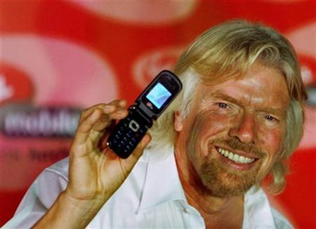 Virgin Group Chairman Richard Branson poses with a mobile phone during the launch of Virgin Mobile services in Mumbai March 2, 2008. REUTERS/Punit Paranjpe