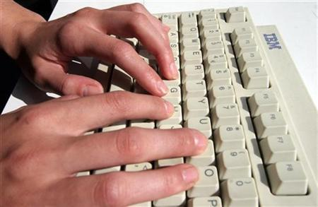 A woman types on a keyboard in this undated file photo. REUTERS/Catherine Benson